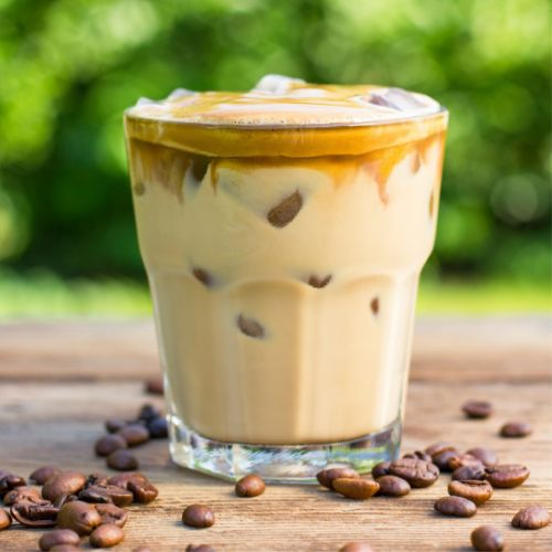 iced mocha in a clear glass with coffee beans